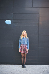 Young beautiful blonde girl posing leaning on a wall with a hearted balloon flying outdoor in the city looking in camera wearing a jeans shirt and a floral skirt
