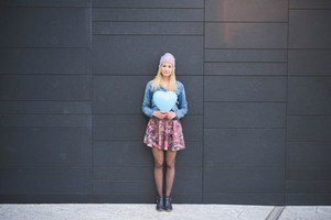Young beautiful blonde girl posing leaning on a wall with a hearted balloon outdoor in the city looking in camera wearing a jeans shirt, a hat, and a floral skirt