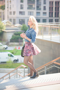 Young beautiful blonde girl posing on a staircase outdoor in the city overlooking on her right wearing a jeans shirt and a  floral skirt - youth, carefreeness, freshness concept