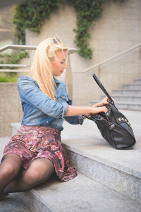 Young beautiful blonde girl posing seated on a staircase outdoor in the city wearing a jeans shirt and a floral skirt searching something in her bag - youth, freshness concept