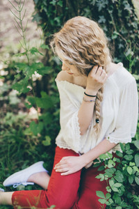 Young beautiful blonde hair woman sitting in the forest overlooking pensive - adventure, magic, dreamy concept