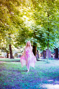 Young beautiful blonde hair woman wearing pink dress standing in the forest - adventure, magic, dreamy concept