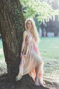 Young beautiful blonde hair woman wearing pink dress standing in the forest leaning on a tree - adventure, magic, dreamy concept