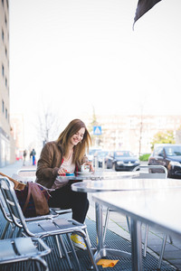 young beautiful blonde hipster woman at the cafe bar using smartphone