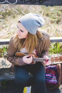 young beautiful blonde hipster woman in the city playing ukulele