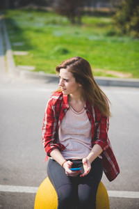 young beautiful blonde hipster woman in the city using smartphone connected online wireless