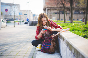 young beautiful blonde hipster woman in the city using smartphone connected online with headphones