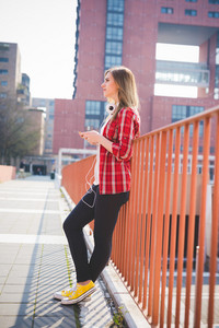 young beautiful blonde hipster woman in the city using smartphone connected online