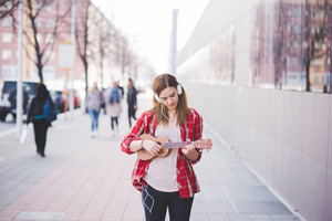 young beautiful blonde hipster woman in the city with ukulele and headphones