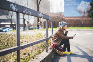 young beautiful blonde hipster woman in the city with ukulele using smartphone connected online