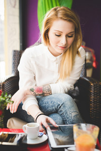 young beautiful blonde straight hair woman in the city sitting at the restaurant using tablet connected online - relax, social network, technology concepts