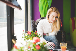 young beautiful blonde straight hair woman in the city sitting at the restaurant using tablet connected online