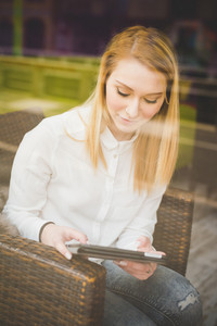 young beautiful blonde straight hair woman in the city sitting at the restaurant using tablet