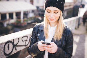 young beautiful blonde straight hair woman in the city using smartphone connected online on internet
