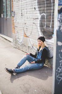 young beautiful blonde straight hair woman in the city using smartphone connected online sitting in the ground