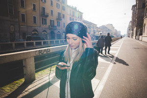 young beautiful blonde straight hair woman in the city with headphones and smartphone listening to music