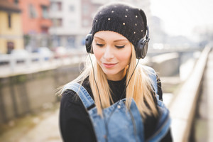 young beautiful blonde straight hair woman in the city with headphones listening to music