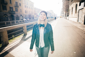 young beautiful blonde straight hair woman in the city with headphones