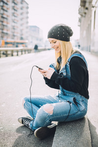 Young beautiful blonde straight hair woman sitting on the ground using smart phone hand hold looking down the screen  smiling - happiness, technology, social network concept