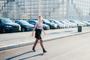 young beautiful blonde woman crossing the street outdoor in the city listening music with earphones - music, technology, relaxing concept