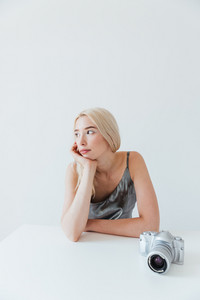 Young beautiful blonde woman in shiny silver dress sitting at the table with camera isolated on the grey background