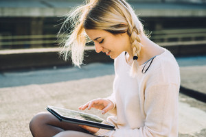 young beautiful blonde woman outdoor in the city using tablet, looking down and tapping the screen - technology, social network, communication concept