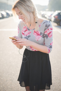 young beautiful blonde woman outdoor in the street of the city listening music and using smartphone with earphones