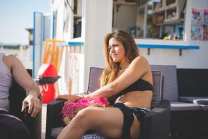 young beautiful brasilian woman at the beach bar in summertime