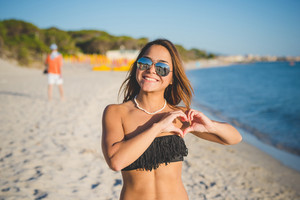 young beautiful brasilian woman making heart love shape with hands at the beach in summertime