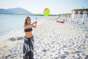 young beautiful brazilian blonde girl at the beach in summertime playing with ball