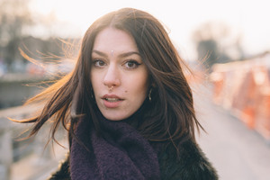 Young beautiful brunette caucasian girl walking down the street in the city, looking astonished at the camerca
