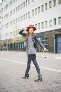 Young beautiful brunette eastern girl walking in the city suburbs dressed with a red hat, a pair of black jeans and a black jacket