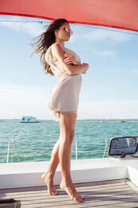 Young beautiful brunette girl in suglasses standing on the yacht