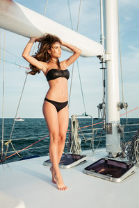 Young beautiful brunette girl in swimsuit posing on the yacht