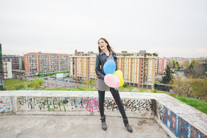 Young beautiful brunette girl playing with colorful baloons in the city suburbs - carefreeness, childhood concept