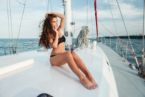 Young beautiful brunette girl talking on the phone while sitting on the luxury yacht