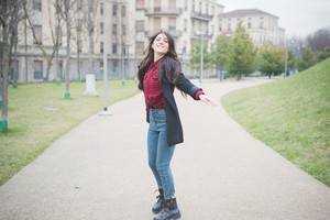 young beautiful brunette long hair model woman feeling free with arms wide open in the city in winter - concept of emancipation, carefreeness, freedom