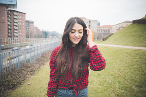 young beautiful brunette long hair model woman touching her hair in the city in winter smiling - Concept of humans emotions - dressed with black coat and checked red shirt
