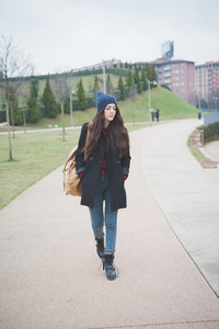 young beautiful brunette  long hair pensive woman walking in the city in winter outdoor looking downward - concept of humans emotions