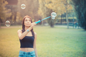 young beautiful brunette straight hair woman blowing soap bubbles outdoor