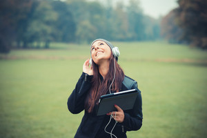 young beautiful brunette straight hair woman in the park during autumn season - listening music with headphones and using tablet device connecting internet wireless