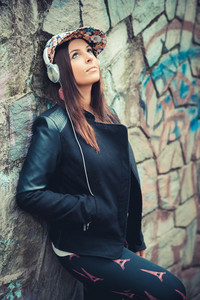young beautiful brunette straight hair woman in the park during autumn season - listening music with headphones