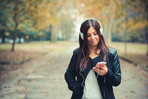 young beautiful brunette straight hair woman in the park during autumn season - listening to music with headphones and smartphone