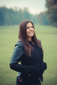 young beautiful brunette straight hair woman in the park during autumn season