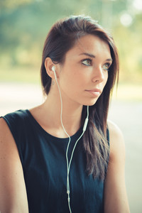 young beautiful brunette straight hair woman listening music outdoor