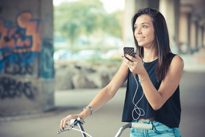 young beautiful brunette straight hair woman using bike and smartphone listening music outdoor
