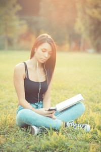 young beautiful brunette straight hair woman using tablet and smartphone sitting on grass outdoor