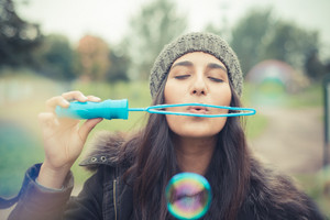 young beautiful brunette woman blowing bubbles soap in the city