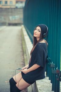 young beautiful brunette woman girl listening music headphones outdoor