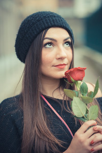 young beautiful brunette woman girl with red rose outdoor